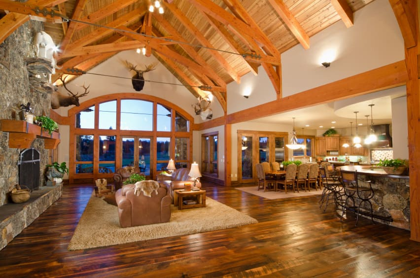 A spacious great room boasting a living space under the home's tall wooden vaulted ceiling with exposed beams. The area features a large stone fireplace and an elegant sofa set on top of a brown area rug covering the hardwood flooring.