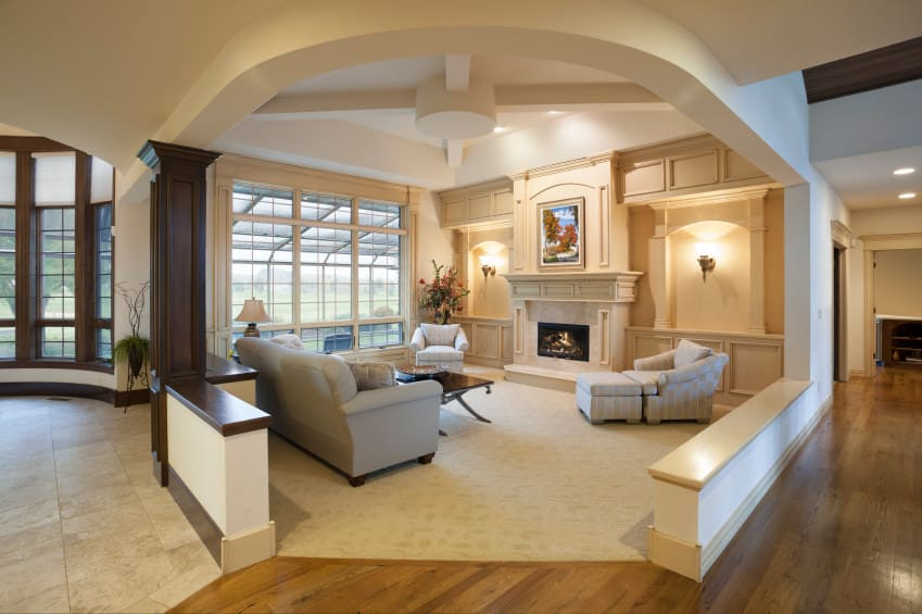 A custom living room featuring a cozy set of seats and a fireplace in front. The area is lighted by wall lights and recessed ceiling lights.