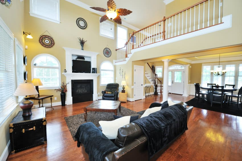 This great room boasts a living space set under the home's two-storey ceiling. The area has a leather couch and a fireplace.