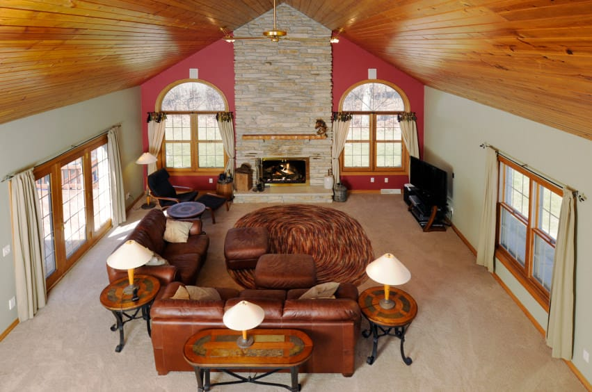 Large living room boasting a tall vaulted ceiling and carpeted flooring. It has a pair of leather couches with matching brown ottomans, along with a fireplace.