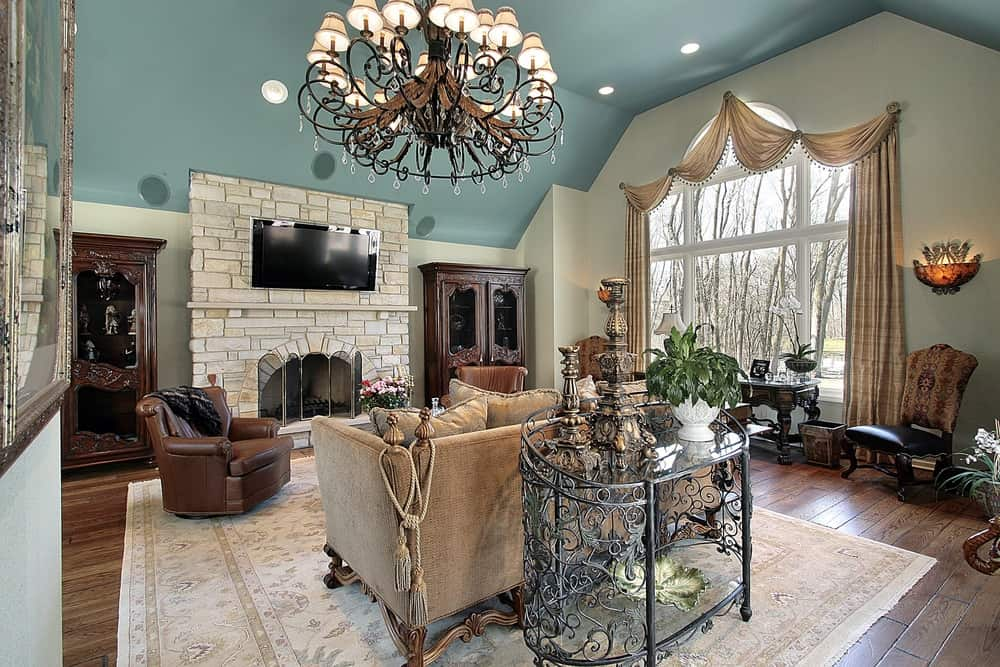 A beautiful large living room with green ceiling and hardwood flooring. The room has a brick fireplace with a TV on top. The room is lighted by a fancy chandelier just above the sofa set.
