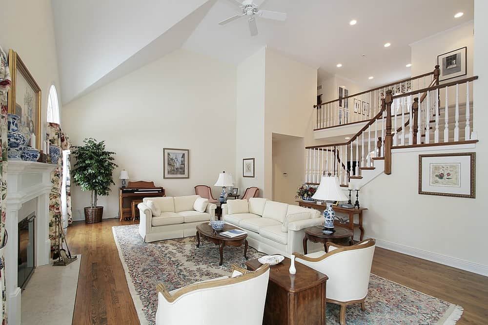 Large living space featuring a white sofa set with a pair of white chairs set on top of a classy rug covering the hardwood flooring. The room also has a fireplace.