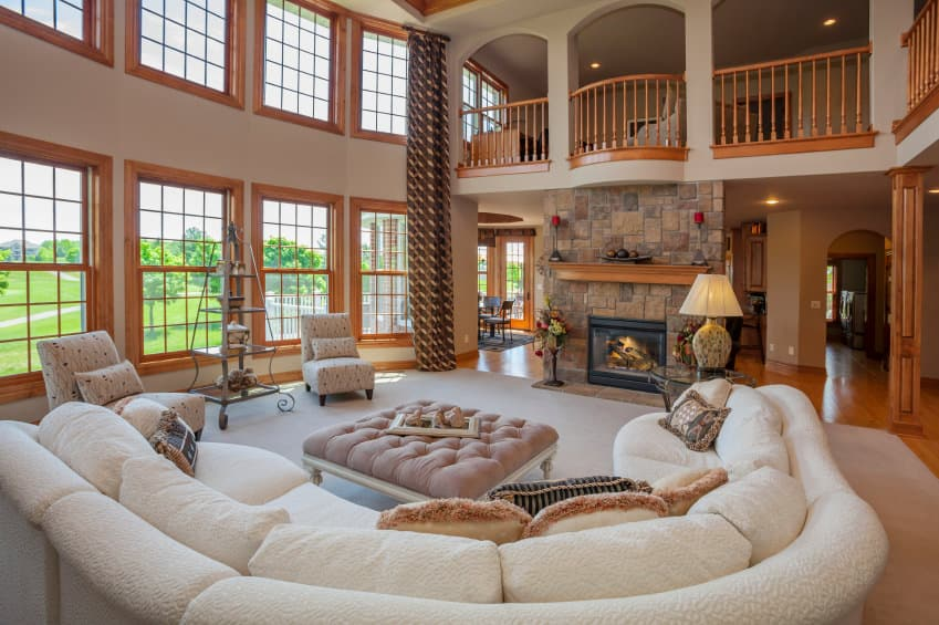 Large formal living room with a large curved comfy sofa set along with an elegant pair of chairs and a stone fireplace. The living space is set under the home's two-storey ceiling.