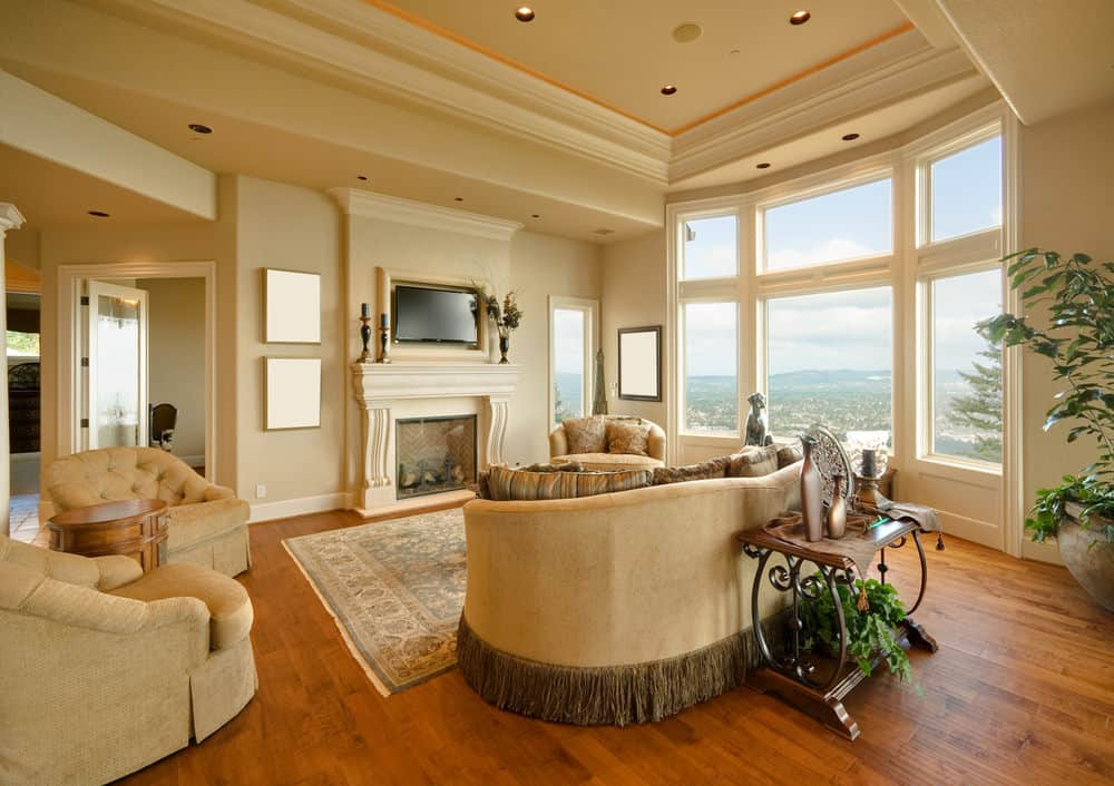 Large living room with a beautifully-designed ceiling along with hardwood flooring. The area has a set of classy seats, a fireplace and a TV on the wall.