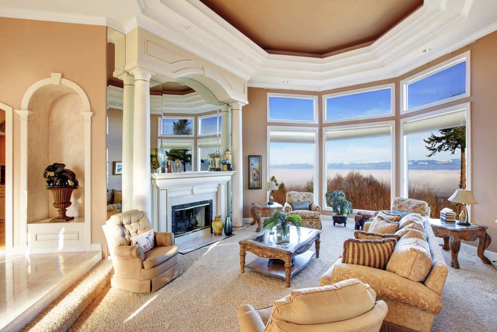 Large living room featuring a stunning tray ceiling and carpeted flooring. The area has elegant seats and a classy center table, along with a fireplace in front.