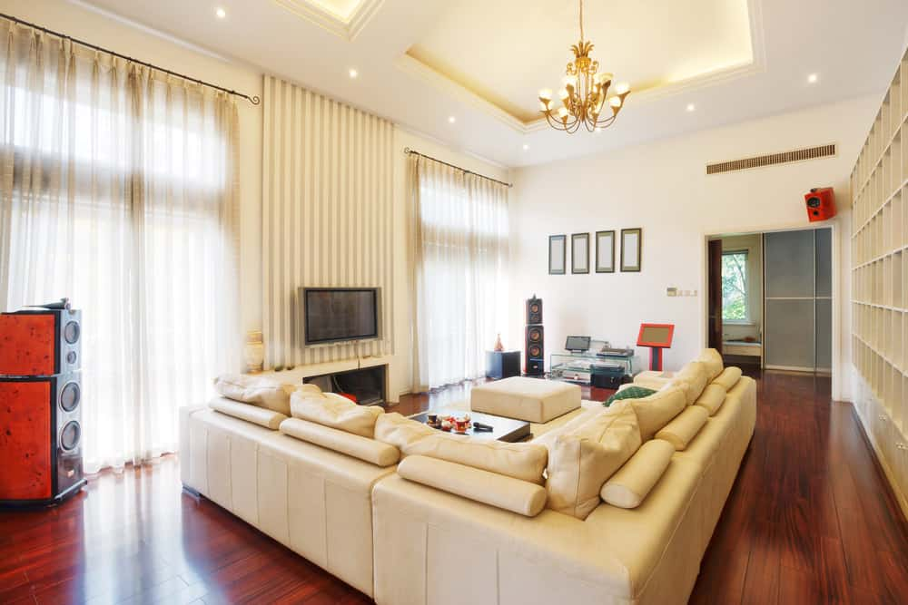 Large family living space with an L-shaped sofa set, a fireplace and a widescreen TV just above it. The area is lighted by a gorgeous chandelier hanging from the tray ceiling.