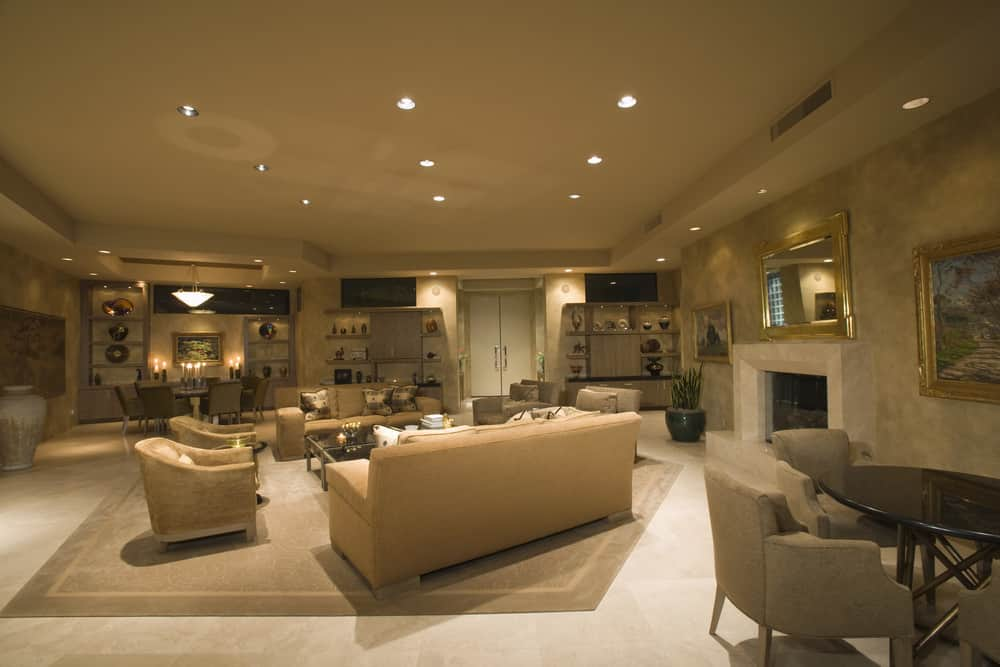 Huge living space featuring a set of classy seats on top of a stylish area rug. The space has a large fireplace and a tray ceiling lighted by recessed lights too.