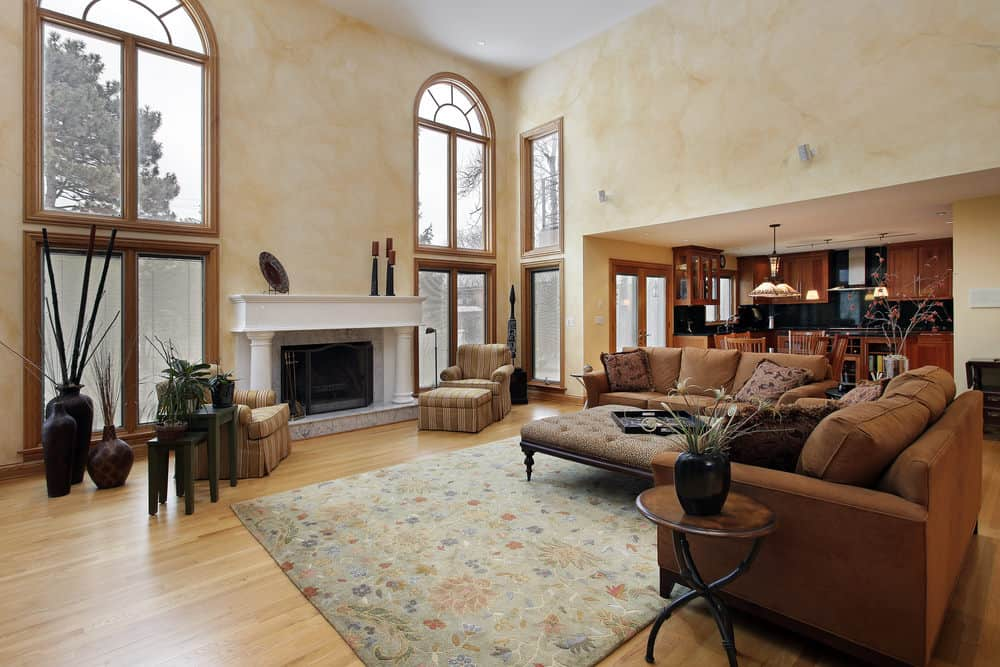 Large formal living room with a modish brown L-shaped sofa set along with a fireplace situated under the home's high ceiling.