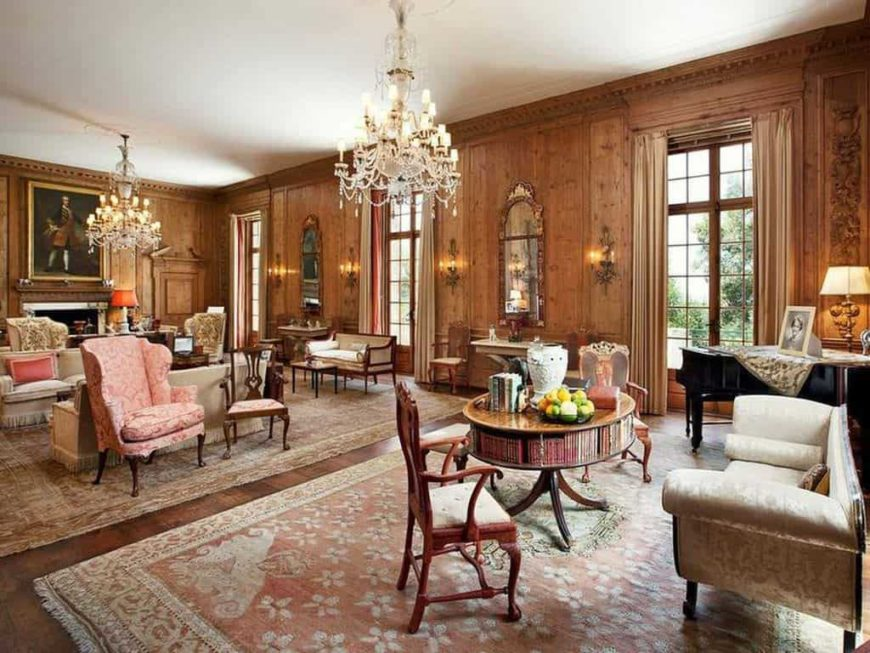 Huge living room with brown walls and hardwood floors. The room is lighted by glamorous chandeliers. The area offers classy seats and a fireplace, along with a beautiful black piano on the side.
