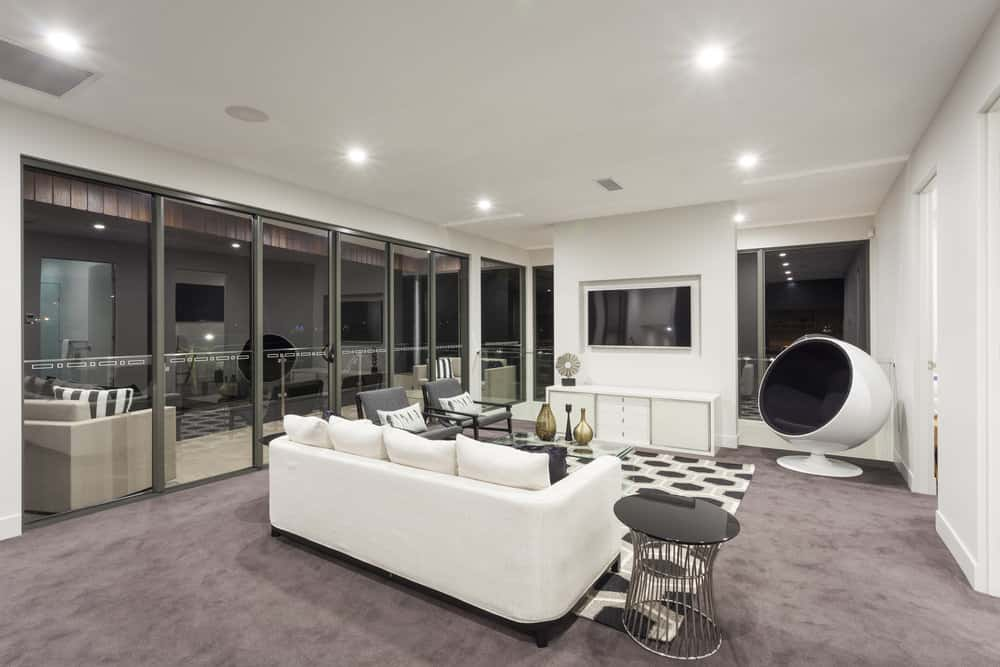 Large modern living room featuring gray carpet flooring and glass windows. The room offers a white couch and a widescreen TV on the wall.