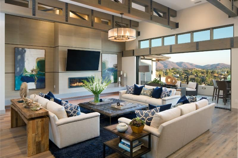 Large family living space boasting a large flat-screen TV just above the modern gas fireplace. The area offers a set of white couches and a fancy ceiling light.