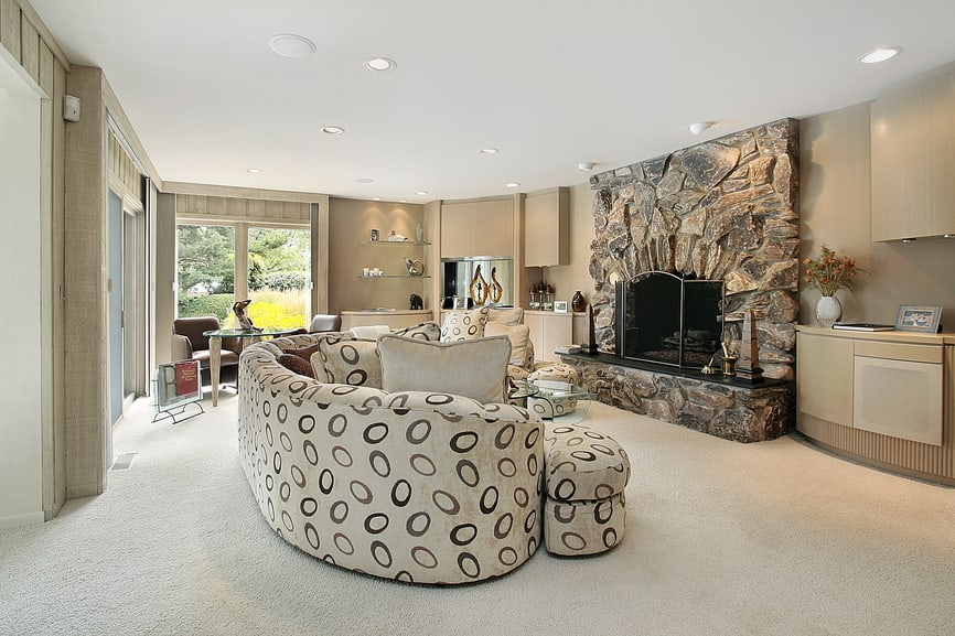 Large formal living room featuring a luxurious sofa set and a large stone fireplace that looks very elegant.