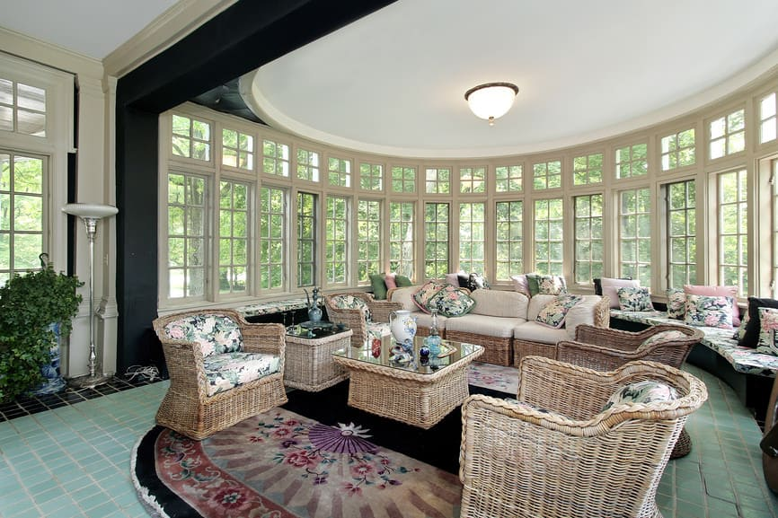 A large glamorous living room boasting a set of rattan-framed seats and center table set. The area's ceiling looks absolutely gorgeous and the windows surrounds it look so classy.