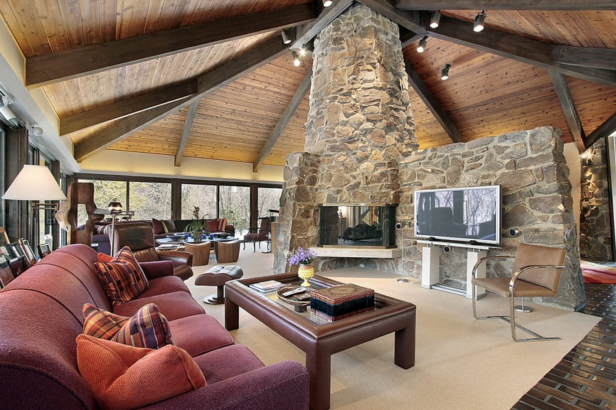 Large family room featuring a red sofa set under the home's wooden ceiling with exposed beams. There's a large widescreen TV in front, along with a fireplace beside it.