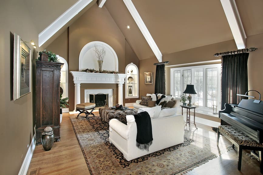 Large formal living room surrounded by brown walls and vaulted ceiling. The room features a black piano the side and a large fireplace.
