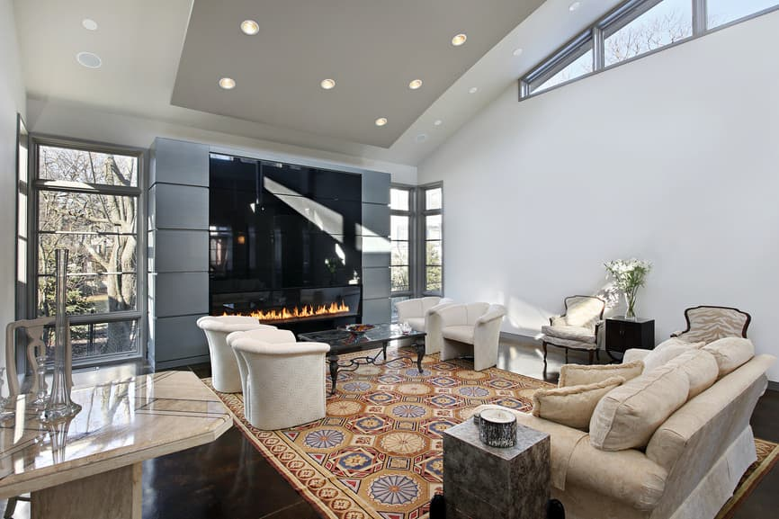 Large modern formal living room featuring a classy sofa set and a stylish area rug covering the gorgeous tiles flooring. The room also has a modern gas fireplace.
