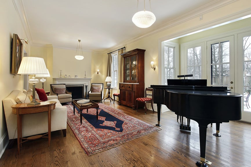 Large formal living room boasting a black grand piano and a classy sofa set along with a fireplace.