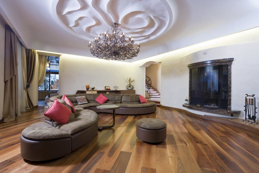 Large modern living space featuring hardwood flooring and a beautifully decorated ceiling lighted by a stunning chandelier. The room offers modern sofa set.