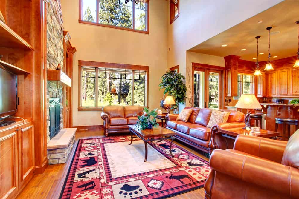 This great room boasts a large living space under the home's high ceiling. The living space has brown leather seats, a large area rug and a large stone fireplace.