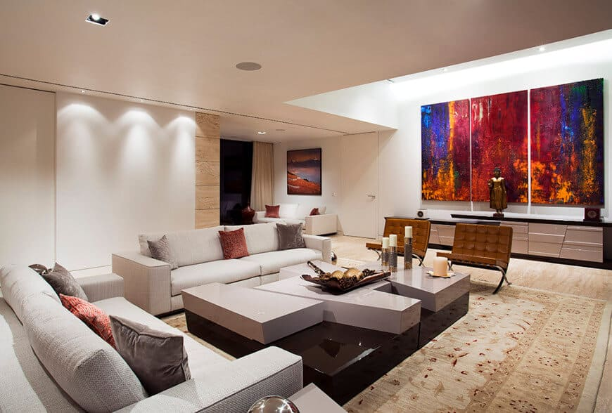Large modern living room featuring a modish sofa set and a very attractive center table set on top of a large area rug.