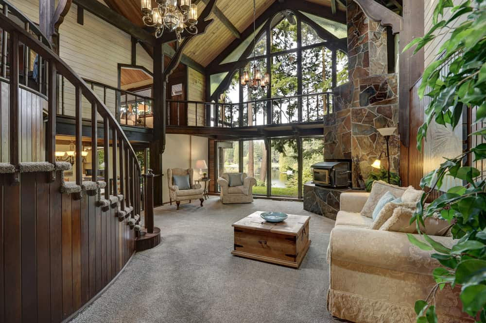 Large rustic living room with a tall vaulted ceiling with exposed beams. The room has a stone fireplace and carpeted flooring.
