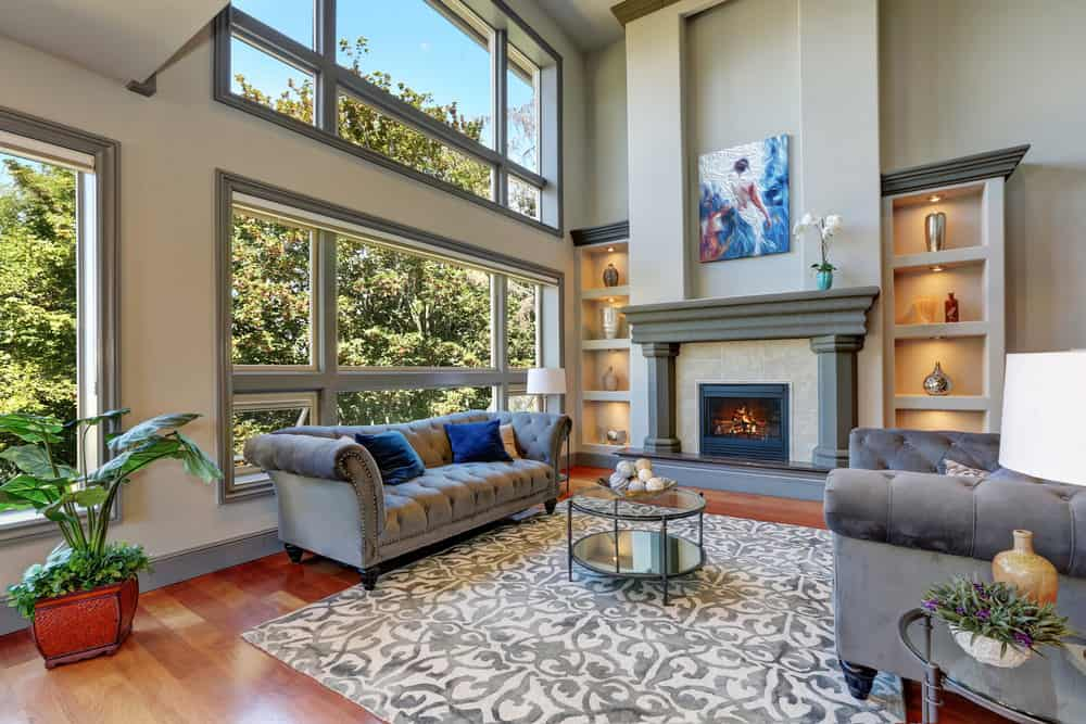 Large formal living room featuring a couple of elegant gray couches and a fireplace. The room has a tall ceiling and a stylish area rug.