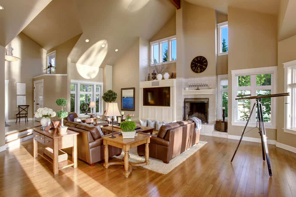 Spacious family living room featuring a set of brown seats, a wooden side and center tables and a fireplace, alongside a large widescreen TV.