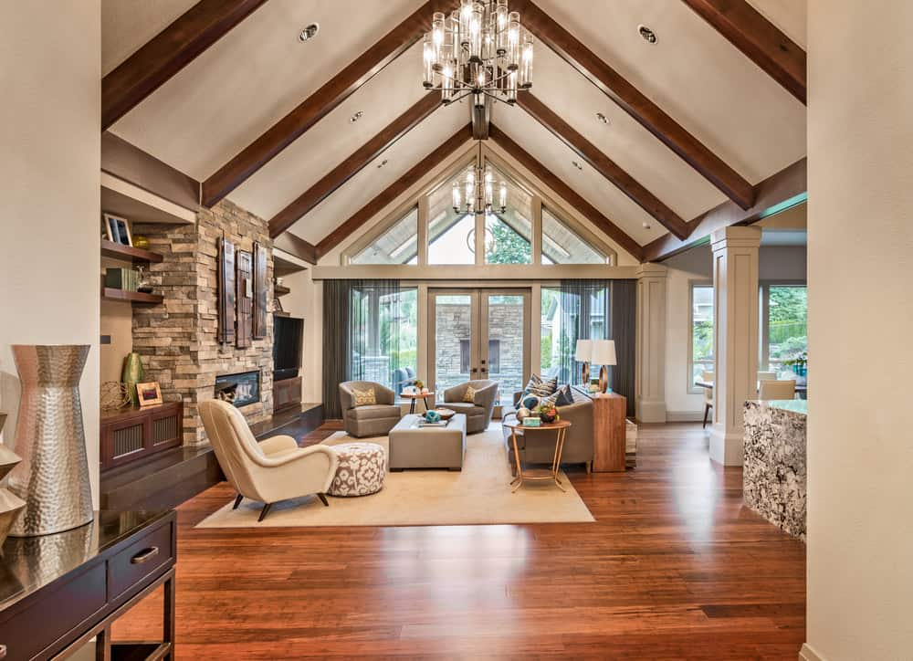 A spacious family living room featuring hardwood flooring and a vaulted ceiling with beams. The room has a set of classy seats and a fireplace lighted by fabulous ceiling lights.