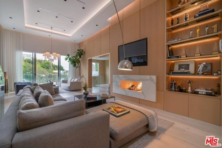 Large modern living room featuring a white tray ceiling. The room has a large gray sofa set and has a modern fireplace in front, along with a large widescreen TV just above it.