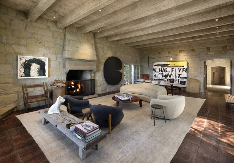 A spacious rustic formal living room with stone walls and a wooden ceiling with beams. The room has a modern sofa set and a fireplace.
