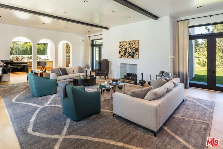 Large formal living room featuring a pair of cozy couches and chairs set on top of a stylish area rug. There's an elegant black piano and a fireplace.