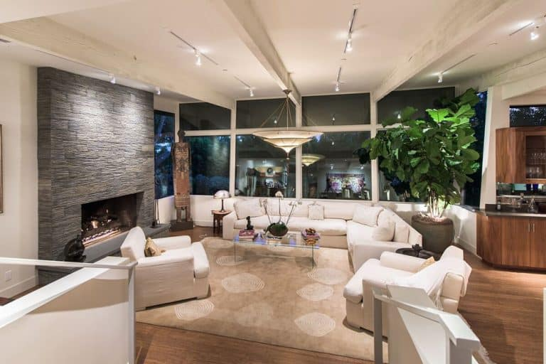 Large living space with a white sofa set and a fireplace. The room is lighted by fancy ceiling lights and has a fireplace too.