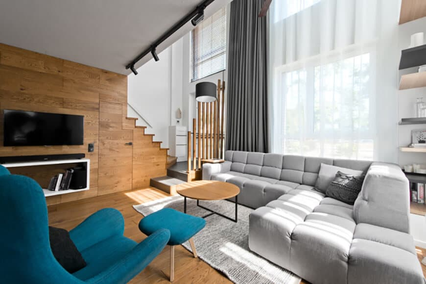 This living room boasts a luxurious gray sofa set lighted by track lights. The room has a widescreen TV on the wooden wall.