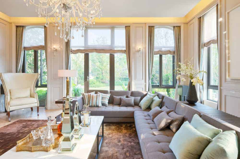 A living room surrounded by beautiful walls and a gorgeous ceiling. The area features a large cozy gray sofa set lighted by a glamorous chandelier.