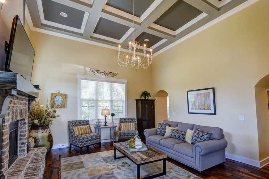 Large family living room situated under the home's gorgeous coffered ceiling lighted by a fancy chandelier. The area has elegant seats, a large fireplace and a large widescreen TV just above it.