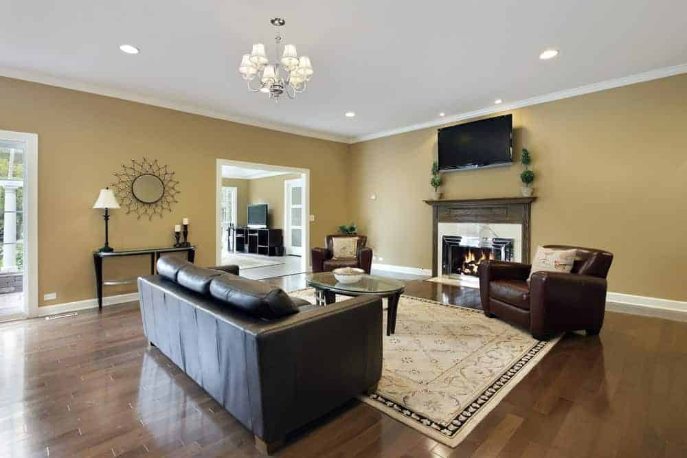 A spacious living room boasting a leather couch and a pair of leather chairs, along with a fireplace and a TV on the wall. The room is surrounded by brown walls and hardwood flooring.