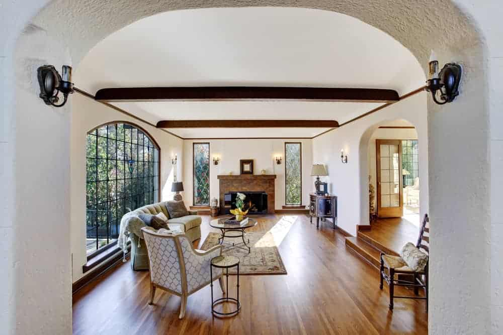 A large Mediterranean formal living room featuring hardwood floors and a ceiling with beams. There's a classy couch and a large fireplace.