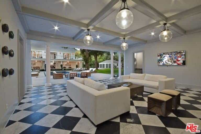 Large modern living room featuring checkered tiles flooring and a coffered ceiling lighted by recessed and pendant lights.