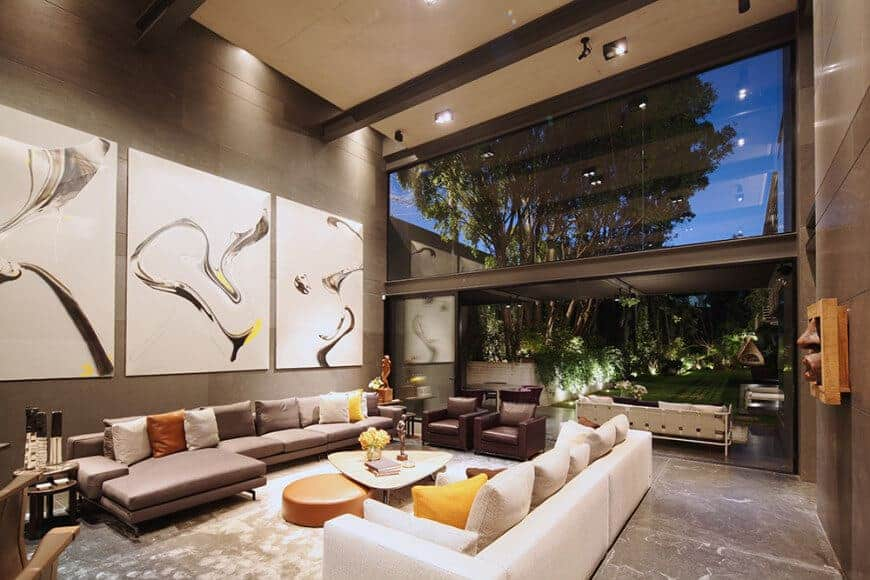 Large contemporary living room boasting two modern sofa sets and a stylish center table set on a classy area rug covering the marble tiles flooring.