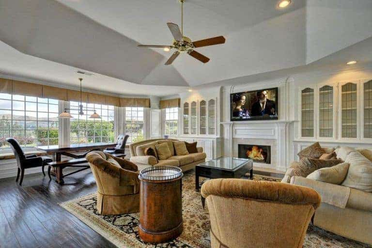 Large living room that offers a set of elegant seats on top of the large area rug. The area also offers a fireplace and a large widescreen TV on top of it.