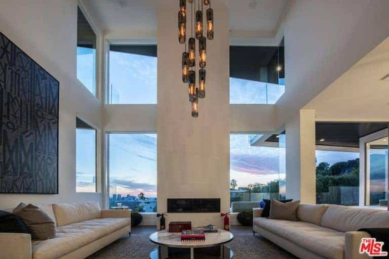 This living room is under the home's high ceiling with stunning ceiling lights hanging from it. The area has two large couches and a modern fireplace.