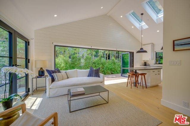 Interior of a farmhouse-style bungalow with pitched ceiling, skylights, accordion and French doors, and French oak floors.