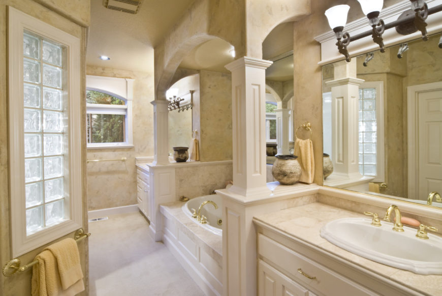 An alcove bathtub is placed in between sink vanities fitted with brass fixtures and hardware that complements the towel rack fixed under the glass block window.