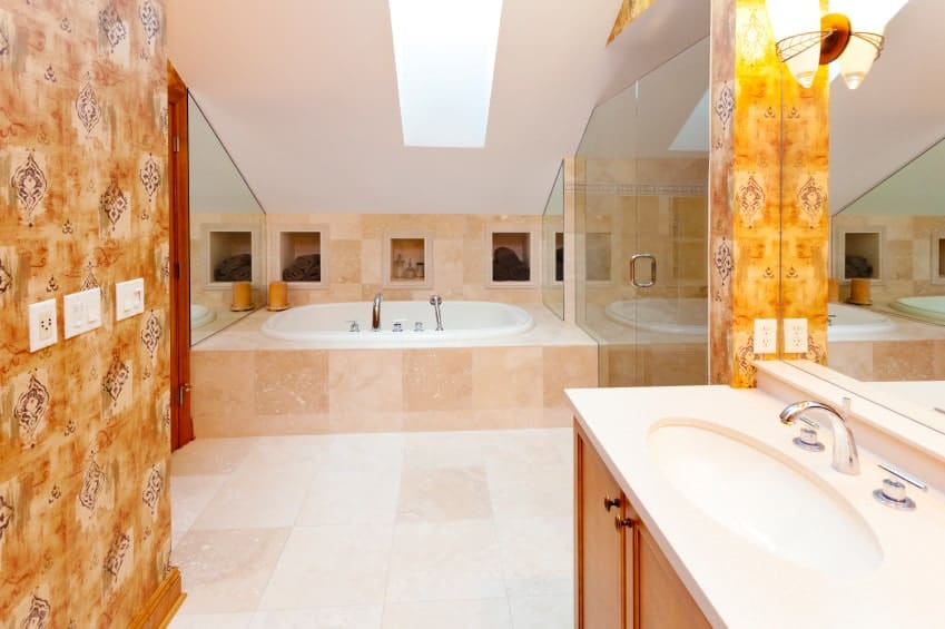 The bright primary bathroom features a sink vanity and deep soaking tub underneath the skylight clad in beige marble tiles that extend to the flooring.