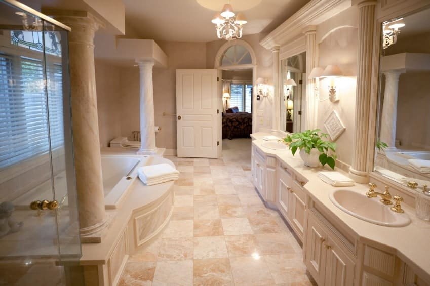 A white wooden door opens to this primary bathroom with a drop-in bathtub and dual sink vanity fitted with brass fixtures and hardware. It is illuminated by a chandelier and matching sconces mounted on the beige walls.
