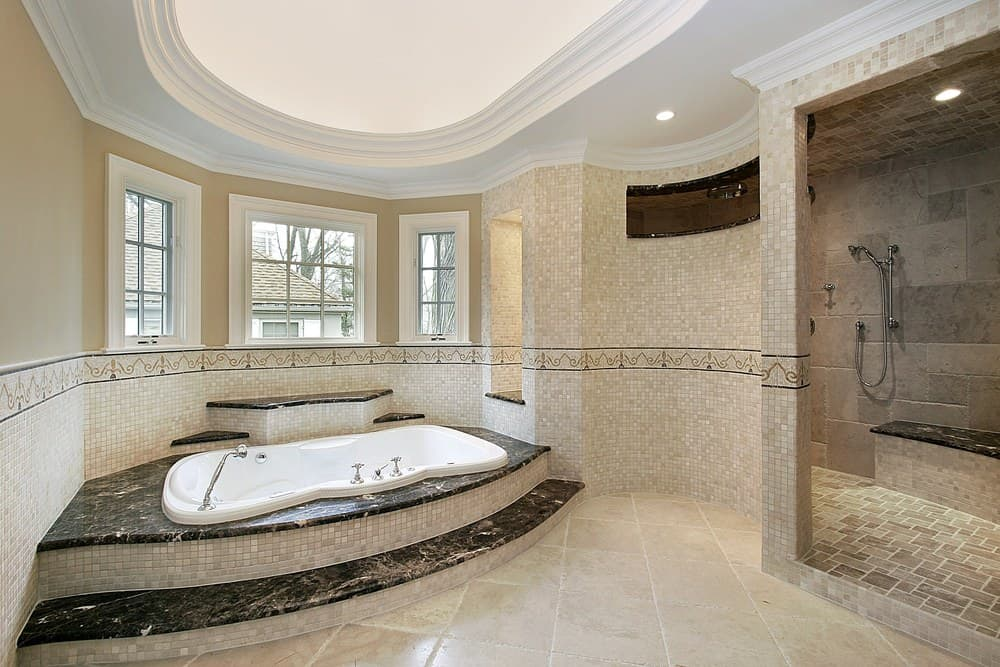 Airy primary bathroom with oval tray ceiling and beige walls dominated by stunning mosaic tiles. It has a drop-in bathtub and an open shower area with a tiled bench topped with a black marble counter.