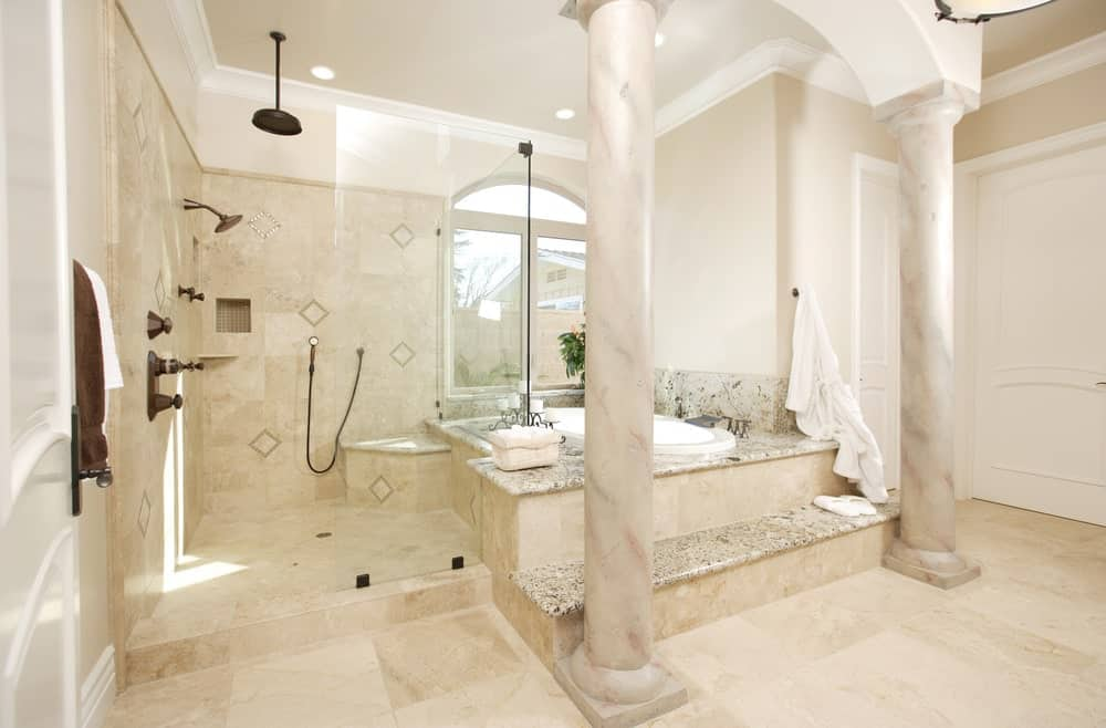 Mediterranean primary bathroom with a walk-in shower and a drop-in bathtub lined with large columns. It has tiled flooring and an arched window that invites natural light in.