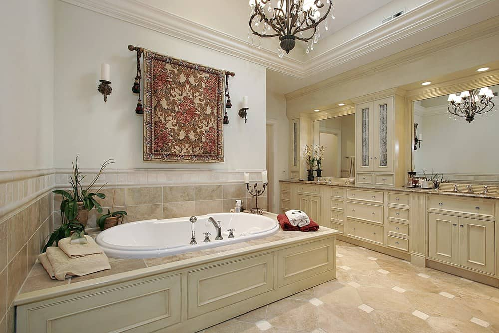Elegant primary bathroom decorated with a fancy chandelier and a gorgeous tapestry with tassels that hung above the deep soaking tub accented with fresh potted plants.