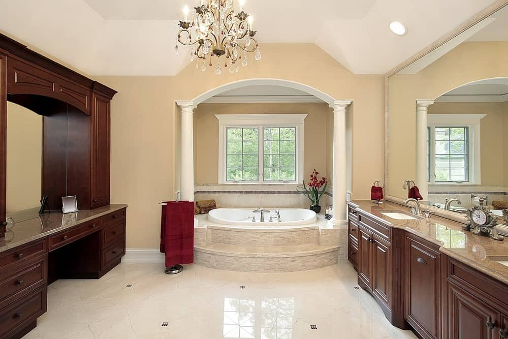 This primary bathroom offers an alcove bathtub and wooden vanities facing each other. It is illuminated by a fancy chandelier that hung from the vaulted ceiling.