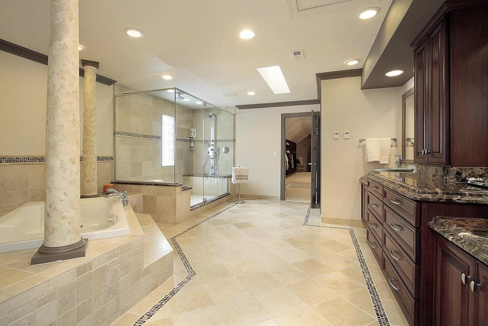 The beige primary bathroom showcases a walk-in shower and drop-in tub lined with a pair of columns. It includes a large dark wood vanity topped with black granite counters.